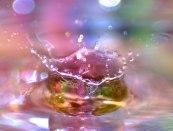 Macro of water drop splashing in multicolored water