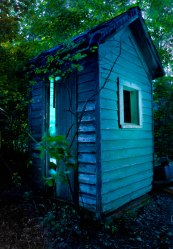 Abandoned glowing outhouse at blue hour