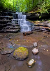 Waterfall in woods with rocks in the foreground
