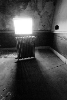 Radiator in abandoned apartment backlit by window