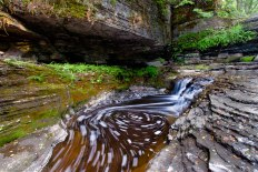 Abandoned adirondack mine with waterfall and foam swirl between rocks