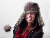 girl laughing while wearing sweater and fur hat
