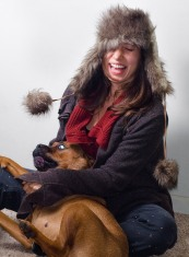 Girl in fur hat and sweater playing with a mastiff puppy