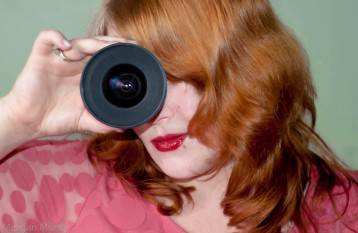 Pale girl with red hair holding lens to eye