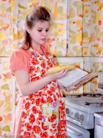 50s housewife with apron in pregnant in the kitchen